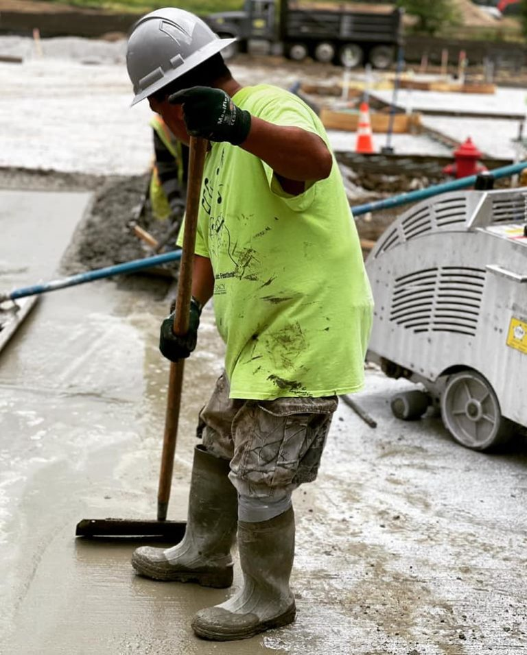 A concrete finisher with CTI Ready Mix uses a long wooden trowel to smooth a newly placed concrete surface.