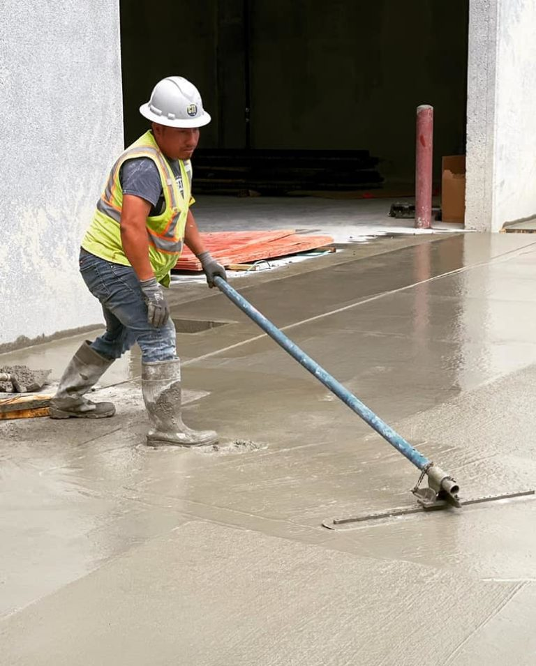 A concrete finisher with CTI Ready Mix gently pushes a metal float over a wet concrete surface.