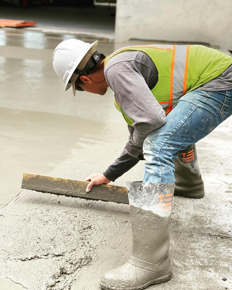 A concrete finisher uses a piece of wood to hand float a newly placed concrete surface.